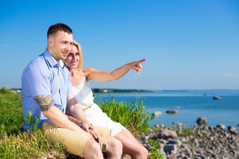 Wakacje pojęcie - szczęśliwa uśmiechnięta para cieszy się dennego widok zdjęcie stock
