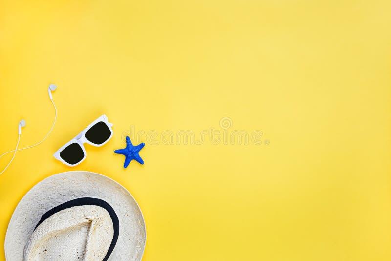 Wakacje t?a poj?cie Słomiany kapelusz, biali okulary przeciwsłoneczni i słuchawki nad żółtym tłem, Odbitkowa przestrze?, mieszkan obraz royalty free