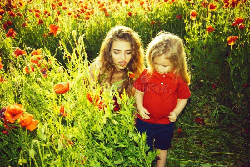 Wakacje w kraju matek dzień, dziewczyna i chłopiec w polu maczek, zdjęcia royalty free