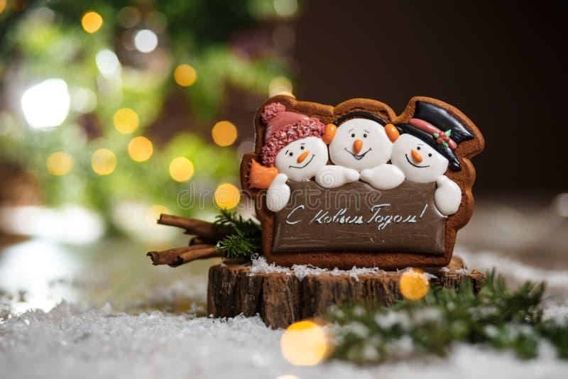 Wakacyjna tradycyjna karmowa piekarnia Miodownika trzy zabawy snowmans w wygodnej ciepłej dekoracji z girlandą zaświecają fotografia stock