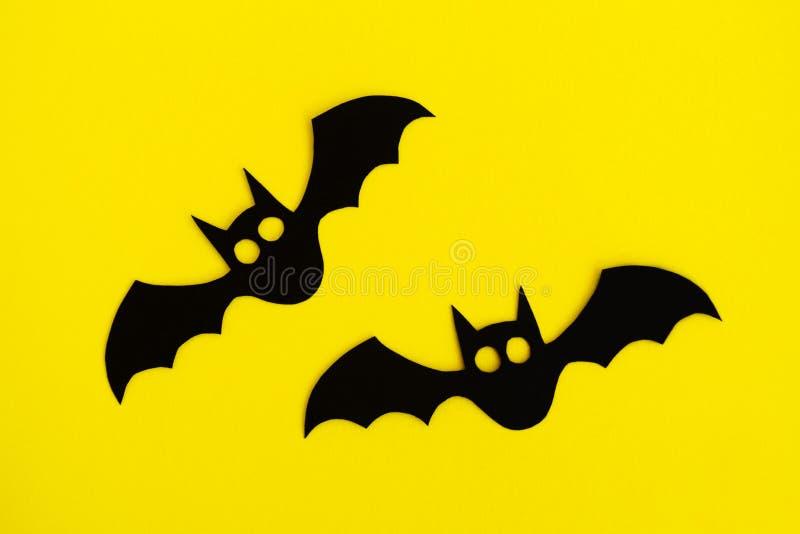 Wakacyjne dekoracje dla Halloween Dwa czerń papierowego nietoperza na żółtym tle, odgórny widok fotografia royalty free