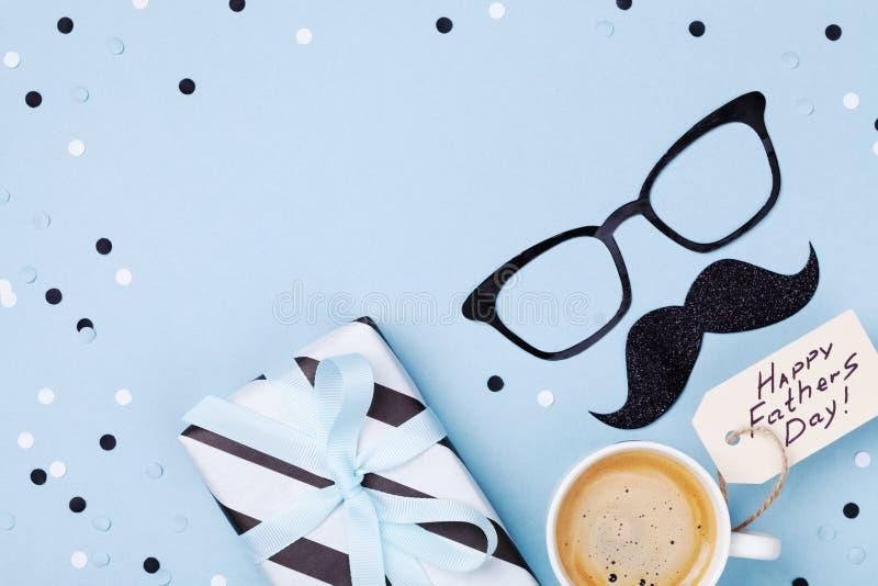 Wakacyjny śniadanie na Szczęśliwym ojca dniu z kawą, prezenta pudełko, śmieszni szkła i wąs na stołowym odgórnym widoku, Mieszkan zdjęcie stock