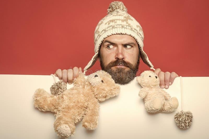Wakacyjny świętowanie i przyjęcie Boże Narodzenia i urodziny Facet z poważną twarzą w zima kapeluszu Modniś z zabawką na czerwien zdjęcie stock