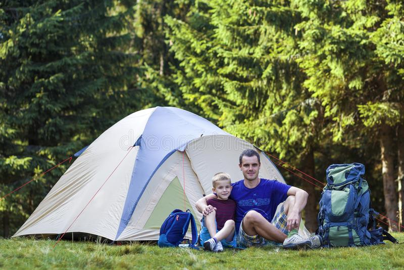 Wakacyjny camping Młoda chłopiec z jego ojca obsiadaniem przed namiotowym bierze odpoczynkiem po wycieczkować w lasowy Podróżnym  obrazy stock
