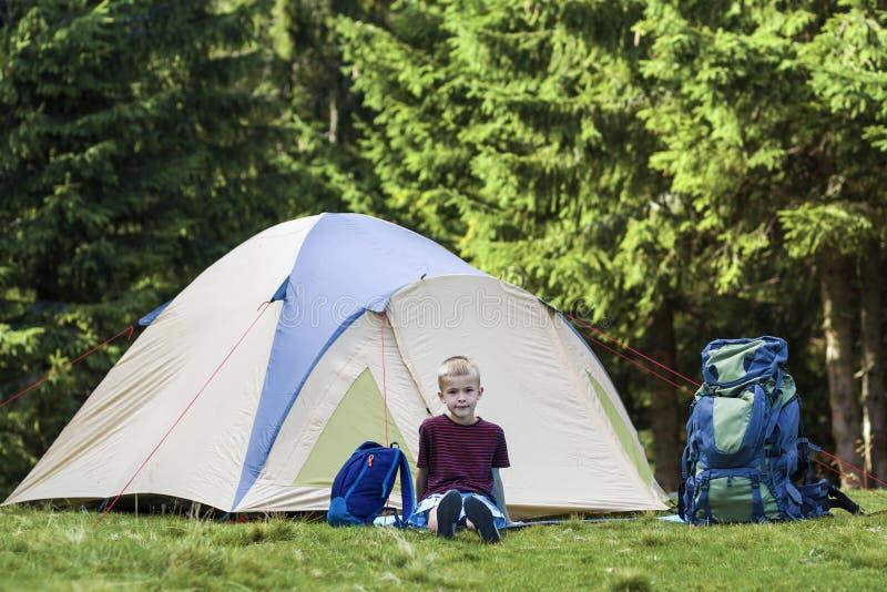 Wakacyjny camping Szczęśliwy młody chłopiec obsiadanie przed namiotowymi pobliskimi plecakami bierze odpoczynek po wycieczkować w obrazy stock