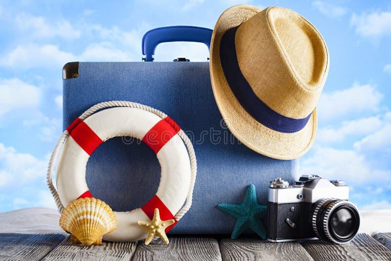 Wakacyjny podróży pojęcie walizka, lato kapelusz, fotografii kamera, lifebuoy -, i skorupy na plażowym i drewnianym tle zdjęcie royalty free