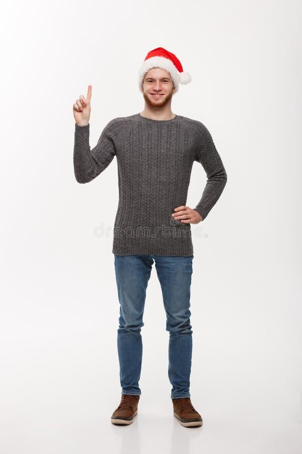Wakacyjny pojęcie - Młody broda mężczyzna w pulowerze cieszy się bawić się palcowy oddolnego i wskazywać zdjęcia royalty free