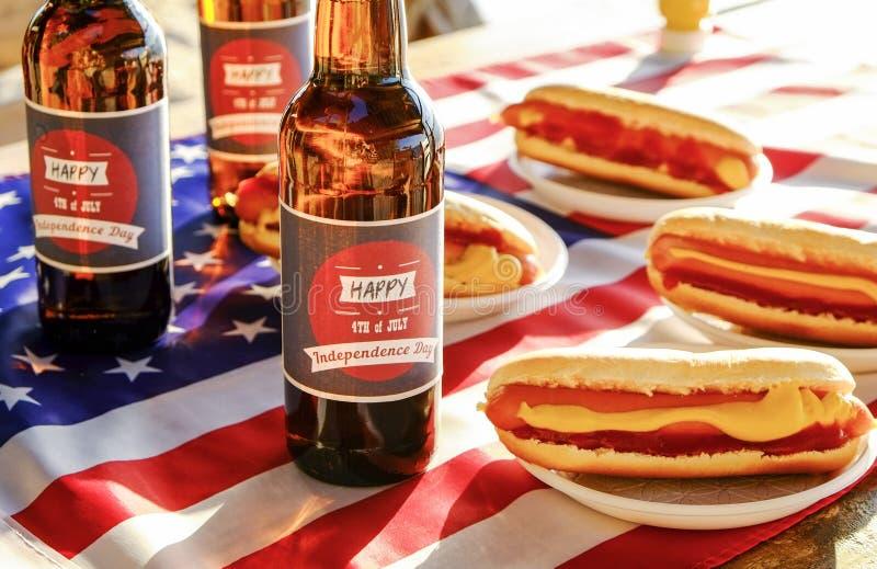 Wakacyjny skład z wieloskładnikowymi butelkami piwo i hot dog, flaga amerykańska Świętować dzień niepodległości usa fotografia stock