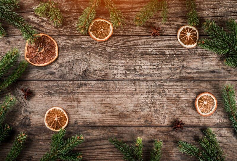 Wakacyjny tło Bożenarodzeniowa jodła rozgałęzia się, świerczyna, jałowiec, jodła, plasterki pomarańcze, sosna rożki z światłem obrazy stock