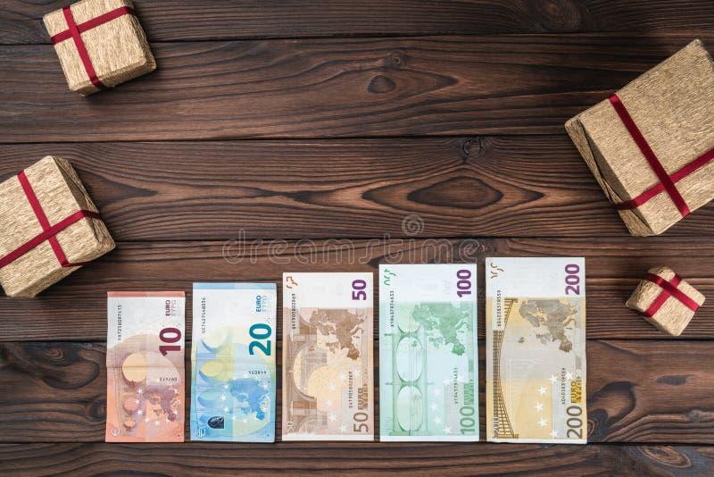 Wakacyjny tło, pieniądze różna wartość i prezenty różni rozmiary, Odgórny widok obrazy stock