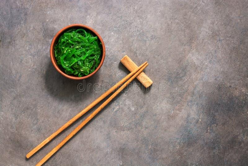 Wakame Chuka ou salada da alga com as sementes de sésamo na bacia no fundo rústico marrom escuro Alimento japon?s tradicional Vis imagem de stock royalty free