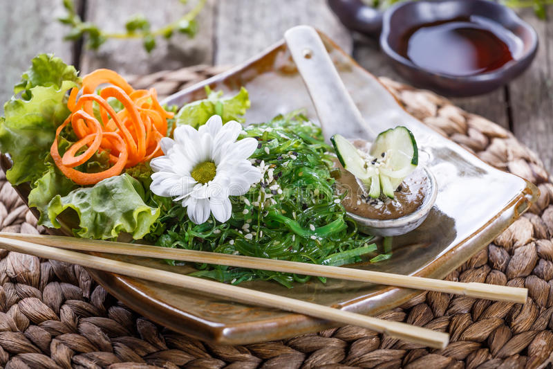 Wakame de salade d'algue dans le plat avec des baguettes sur le tapis en bambou Cuisine japonaise photographie stock