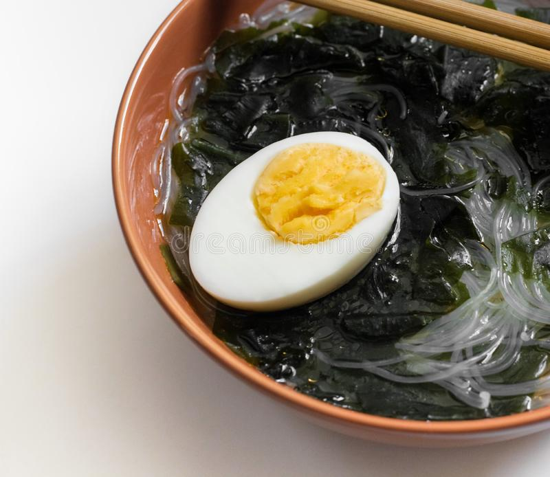 Wakame seaweed soup with noodles and egg in a brown bowl close-up. Traditional Asian food with algae, funchoza and egg. Wholesome. Food royalty free stock photos