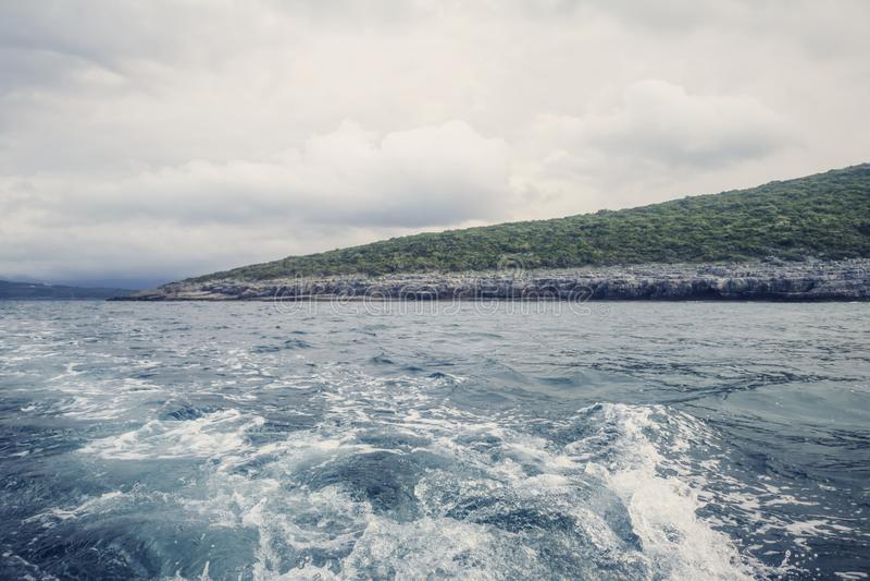 Wake of boat and shoreline, Cloudy Sky obraz stock