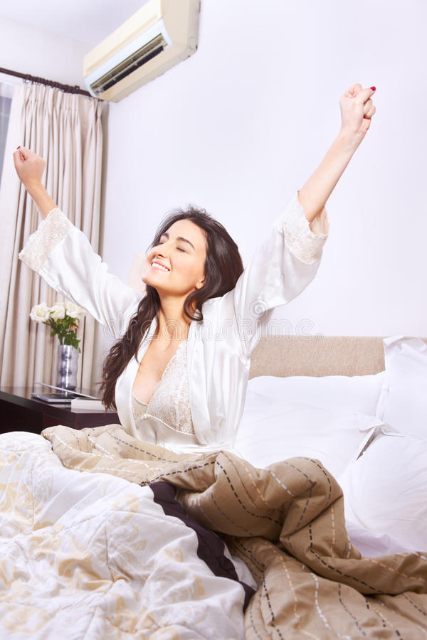 Wake up. Young woman stretching when wake up in the morning stock photo
