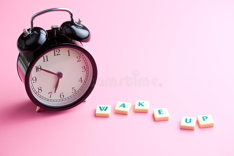 Wake up. alarm clock on pink background. Wake up. The alarm clock on pink background royalty free stock images