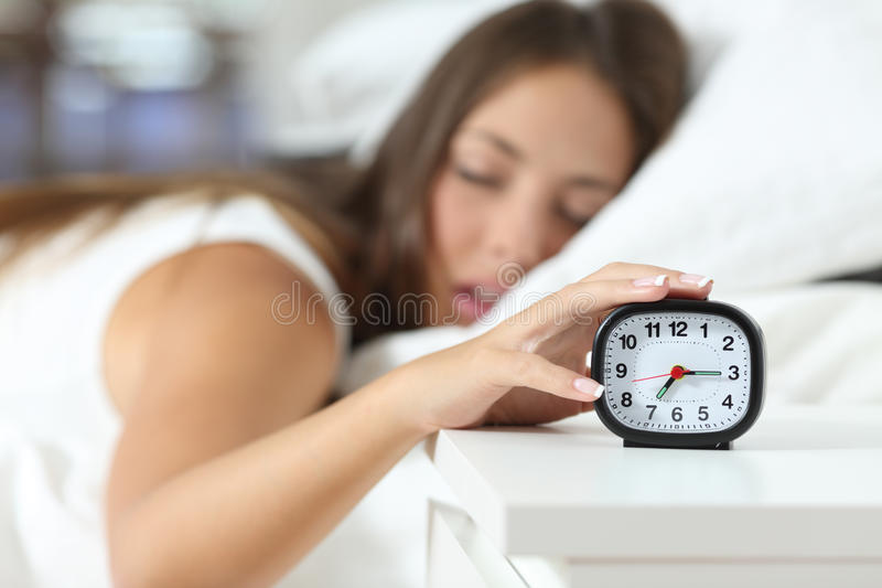 Wake up of an asleep girl stopping alarm clock royalty free stock photo