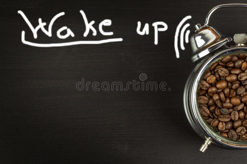 Wake up. Retro alarm clock with coffee beans. Morning coffee after waking up. royalty free stock images
