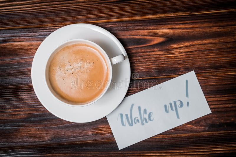 Wake up text near cup of coffee. Font of lettering word on white paper by calligrapher. Morning, handwriting, lettering, concept royalty free stock photography