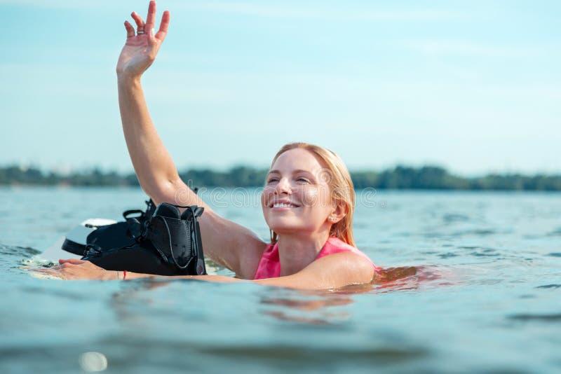 Wakeboarder alegre bonito de sorriso da mulher que acena sua mão foto de stock