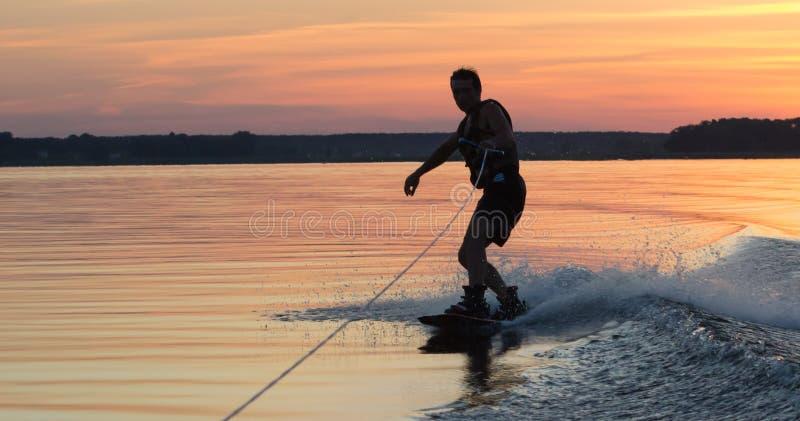 Wakeboarder, der Tricks auf Sonnenuntergang macht stockbilder