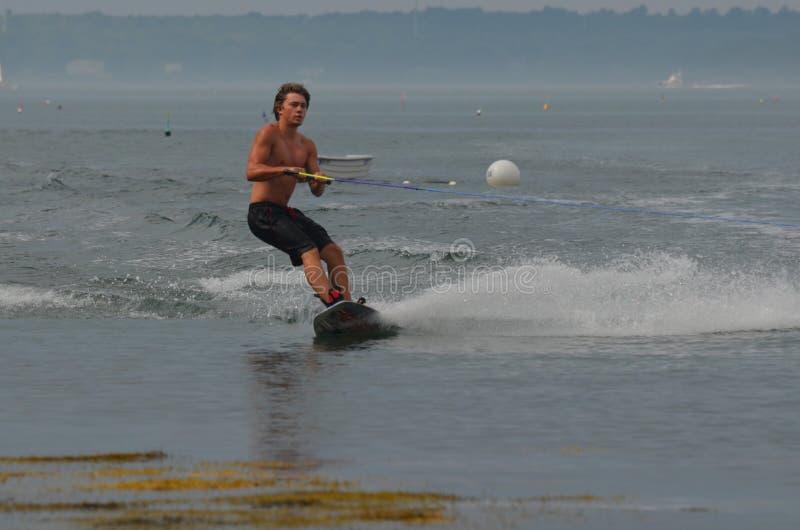Wakeboarder, der um ein Bündel Meerespflanze in Maine schnitzt lizenzfreie stockfotos