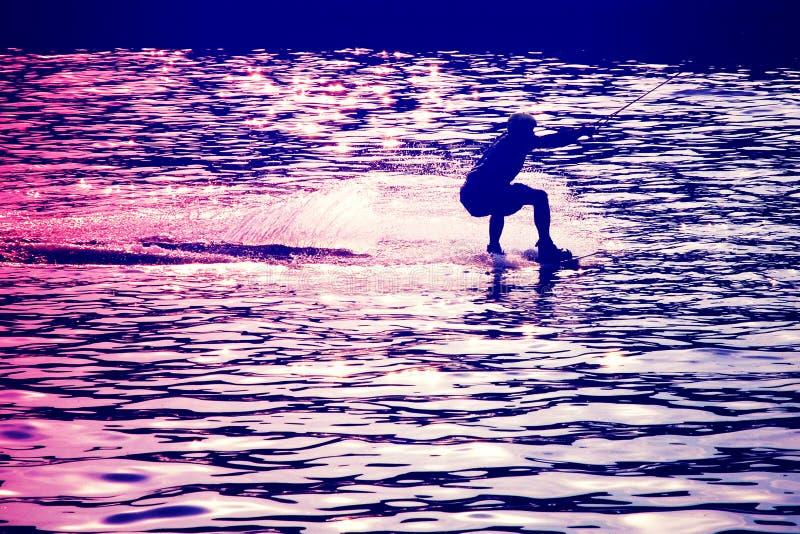 Wakeboarder vor Sprung in den Strahlen der untergehender Sonne lizenzfreies stockbild