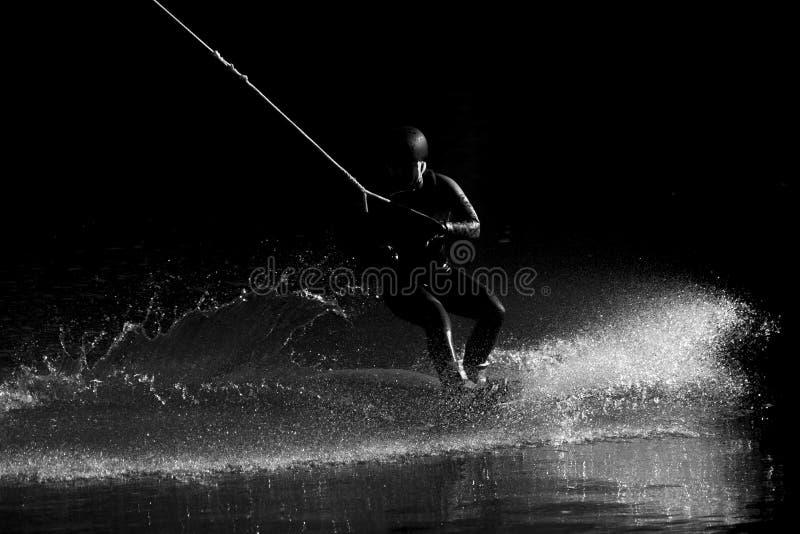 Wakeboarding Siluetta dell'atleta con spruzzata di acqua durante il tramonto fotografie stock
