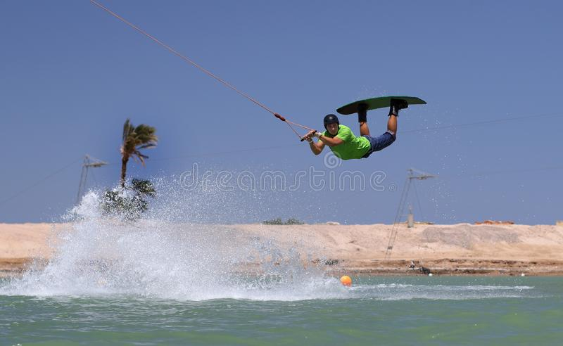 Wakeboarding sportsman jumping high in the cable park, water sports royalty free stock photography