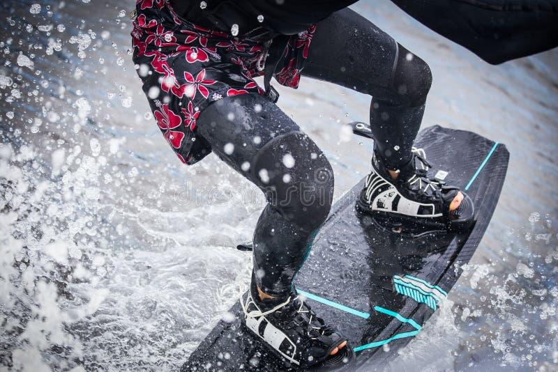 Wakeboardingsmens in een plons van water, slechts benen royalty-vrije stock fotografie