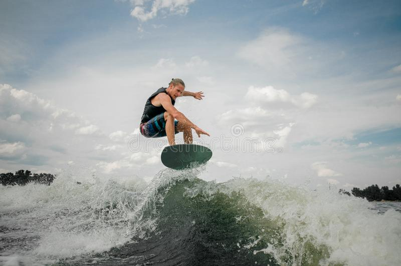 Wakesurf rider jumping on the waves of the river. Young and athletic wakesurf rider jumping on the waves of the river against the blue sky stock image
