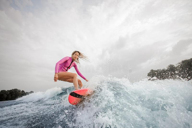 Wakesurfer louro da mulher que monta abaixo do agai de espirro azul da onda foto de stock royalty free