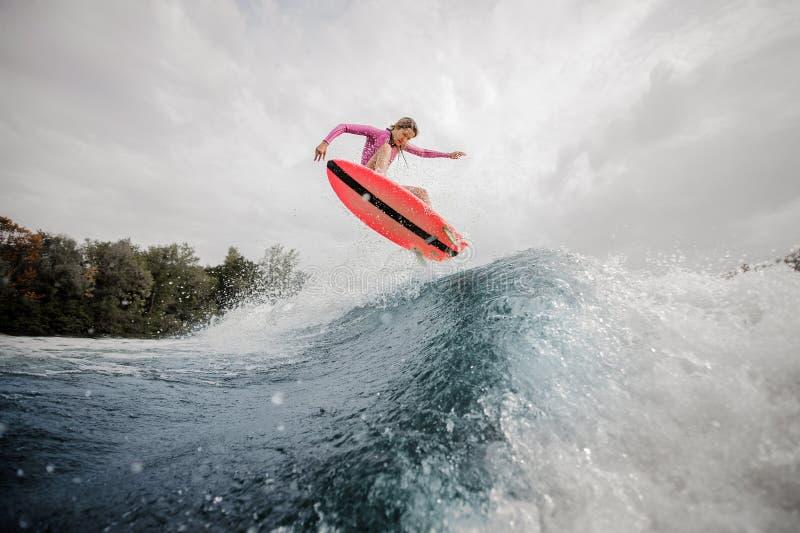 Wakesurfer louro da mulher que salta acima da onda de espirro azul outra vez fotografia de stock royalty free