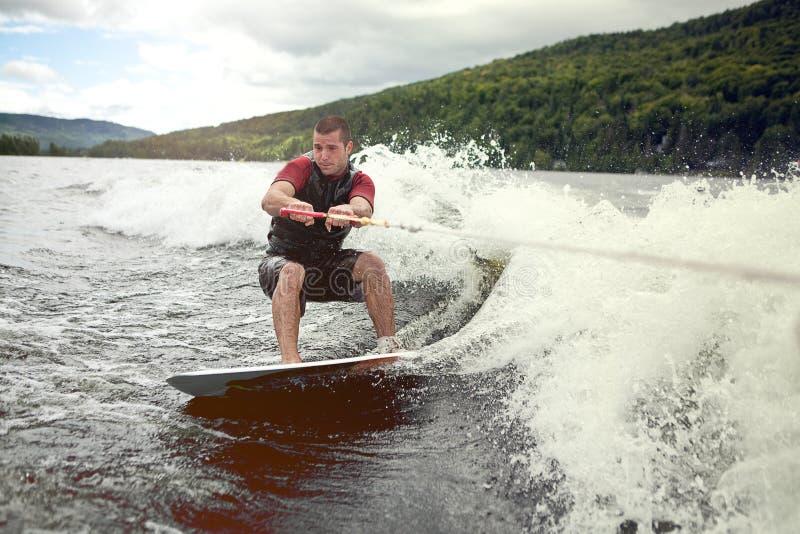 wakesurfing在湖的愉快的英俊的人 免版税库存图片