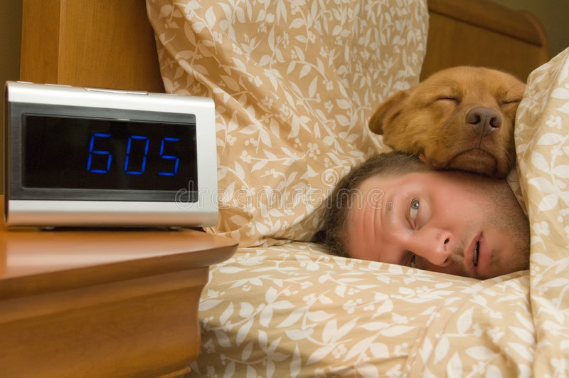 Waking up. Man waking up with dog comfortably sleeping in