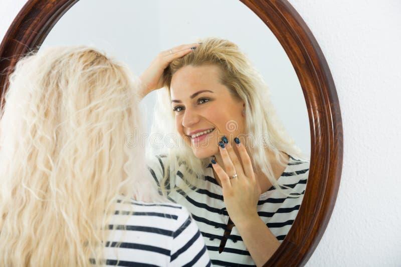 Wakker meisje die in spiegel op muur kijken royalty-vrije stock foto's
