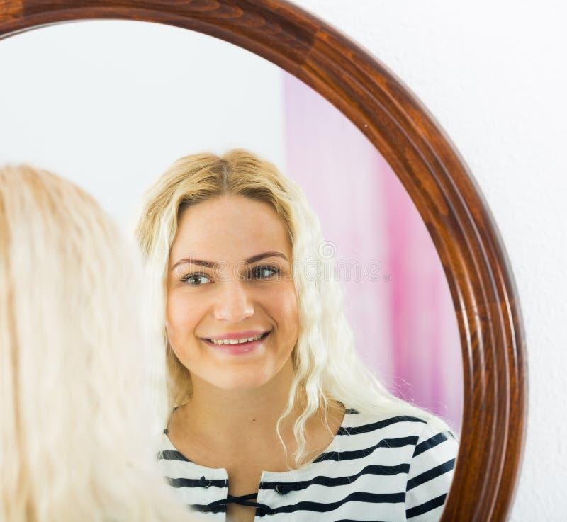 Wakker meisje die in spiegel op muur kijken royalty-vrije stock fotografie