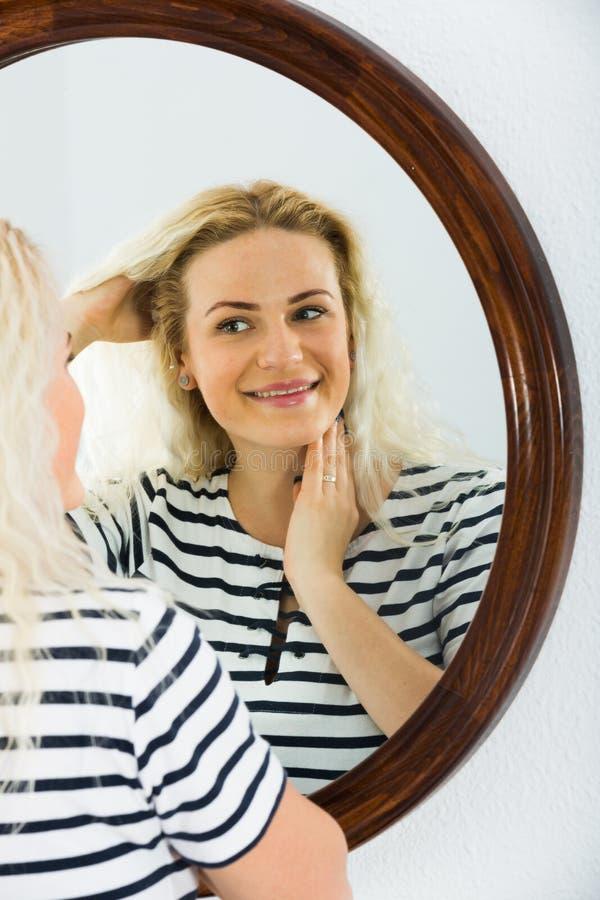 Wakker meisje die in spiegel op muur kijken royalty-vrije stock foto