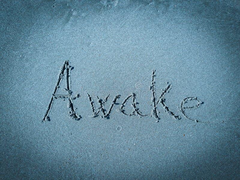 Wakker, woord op blauw zand wordt geschreven dat royalty-vrije stock afbeelding