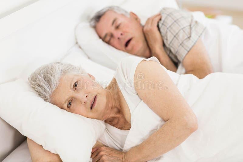 Wakkere hogere vrouw in bed stock fotografie
