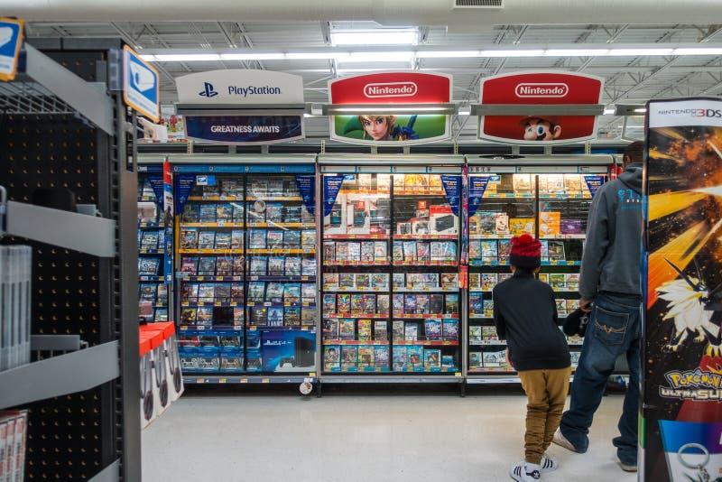 Wal-Mart Video Game Section Little-Jongen die Spelen het Winkelen bekijken stock fotografie