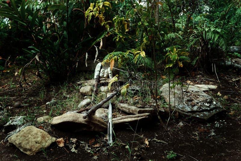 Walaranodorp, Malekula-Eiland/Vanuatu - 9 juli 2016: magische stenen en andere heilige artefacten bij een heilige begrafenisplaat stock afbeeldingen