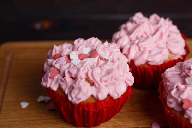 Walentynek babeczki z różowymi śmietanki i cukieru serca dekoracjami obraz royalty free