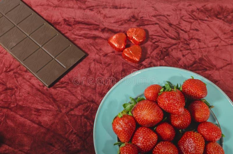 Walentynek czerwone truskawki w cyraneczki błękitnym naczyniu z rozciekłą gorzką czekoladą obraz stock