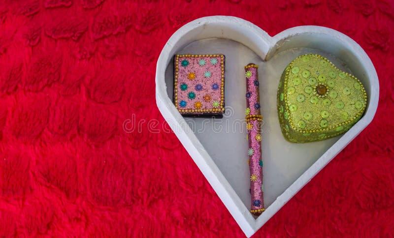 Walentynka dnia dekoracyjny tło, biały serce kształtujący pudełko z notatnikiem, pióro i serce kształtujący pudełko w nim kłaść n zdjęcia stock