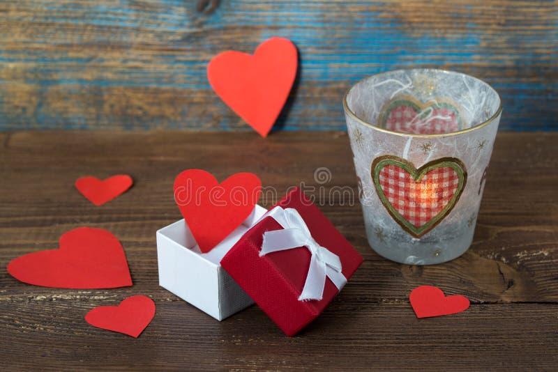 Walentynka dnia karta, czerwoni serca w prezenta pudełku i płonąca świeczka z sercami na drewnianym tle, obrazy stock