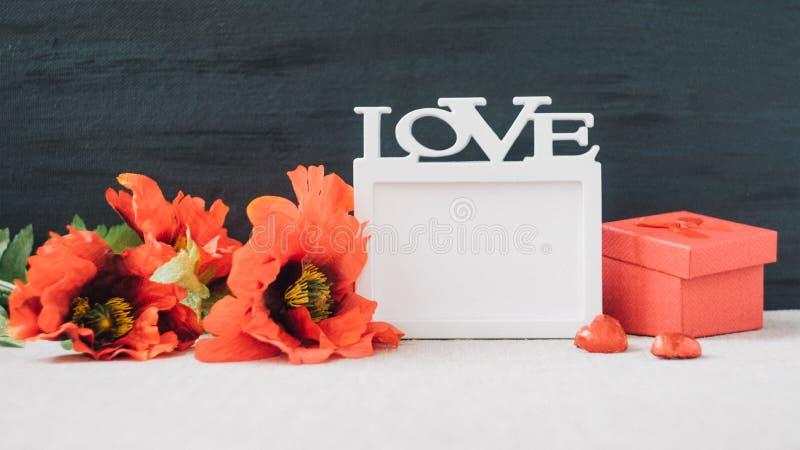 Walentynka dnia mockup z biel ramą z słowem miłość, czerwoni maczków kwiaty i prezenta pudełko na tkaninie i czarnym tle, valenti zdjęcia royalty free