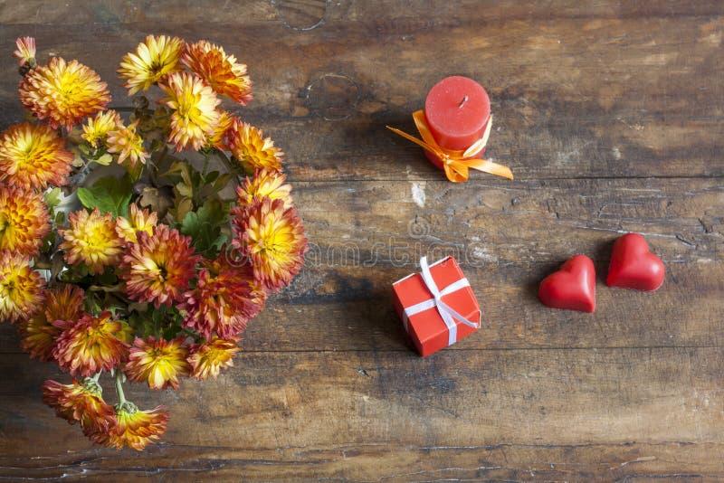 Walentynka dnia prezent, czerwoni czekoladowi serca, świeczka i złota chryzantema na drewnianym tle, obrazy royalty free