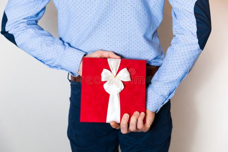 Walentynka dnia prezent, przystojny młody człowiek chuje niespodzianka prezent behing jego z powrotem fotografia royalty free