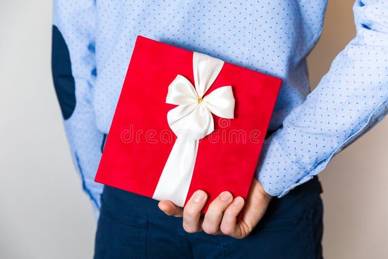 Walentynka dnia prezent, przystojny młody człowiek chuje niespodzianka prezent behing jego z powrotem zdjęcia royalty free